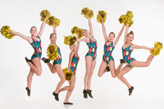 The group of teen cheerleaders jumping at white studio Royalty Free Stock Photography