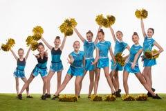 The group of teen cheerleaders posing at white studio Royalty Free Stock Photo