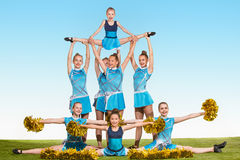 The group of teen cheerleaders posing at white studio Stock Photography