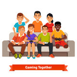 Group of teen friends having a video games party. Big mixed race group of teen friends having a video games party, playing on sofa. Flat style vector Stock Image