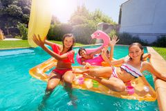 Happy friends lounging on pool floats in summer stock photo