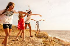 Teens throwing stones over cliff edge at seaside stock photos