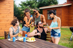 Group of teenage friends drinking beer and eating snacks. Happy group of teenage friends sitting at table drinking beer and eating snacks royalty free stock photography