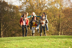Group Of Teenage Friends Having Piggyback Rides. In Autumn Landscape Royalty Free Stock Images