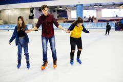 Group of teenage friends ice skating on an ice rink royalty free stock photography