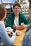 Group Of Teenage Friends Meeting In Cafe And Using Mobile Phones Royalty Free Stock Photos