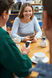 Group Of Teenage Friends Meeting In Cafe And Using Mobile Phones Royalty Free Stock Photography