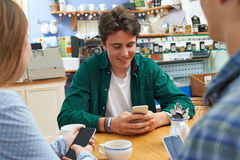 Group Of Teenage Friends Meeting In Cafe And Using Mobile Phones Stock Photography