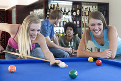 A group of teenage friends playing pool in a bar Royalty Free Stock Image