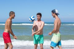 Group teenage friends playing volleyball on beach Royalty Free Stock Photos