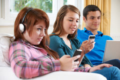 Group Of Teenage Friends Using Digital Technology At Home Royalty Free Stock Images