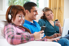 Group Of Teenage Friends Using Digital Technology At Home Stock Photo