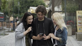 Group of teenage friends using smartphone for entertainment in urban environment having fun stock video