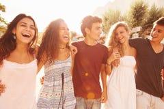 Group Of Teenage Friends Walking Along Street Stock Image