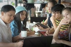 Group of teenage friends working and meeting in team with reports. On wooden table Royalty Free Stock Photo