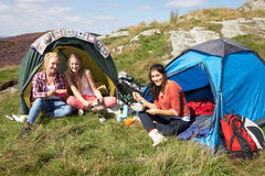 Group Of Teenage Girls On Camping Trip In Countryside. Eating Next To Tents royalty free stock photo