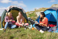 Group Of Teenage Girls On Camping Trip In Countryside. Eating In Tents Stock Photo