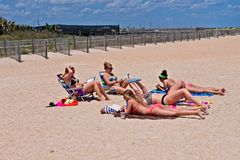 A group of teenage girls lay on the beach. Some are reading.  Background is a wooden fence among blue skies with white puffy clouds Royalty Free Stock Photo