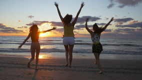 Group of teenage girls running on the beach towards the sea. At sunrise stock footage