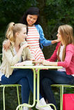 Group Of Teenage Girls Sitting At Outdoor cafe Stock Photography