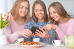 Group of teenage girls with smartphone. Group of teenage girls sitting at table with smartphone Royalty Free Stock Photos