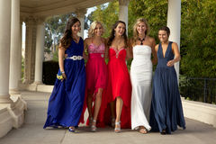 A Group of Teenage Girls walking in their Prom Dresses. A group of beautiful girls at the prom walking, smiling and having fun Stock Photo