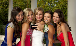 A Group of Teenage Prom Girls Taking a Selfie. Beautiful Teenager girls wearing prom dresses taking a selfie with their phones camera Royalty Free Stock Photography
