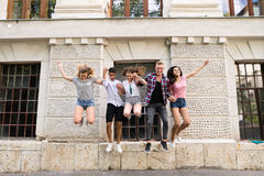 Group of teenage students in front of university jumping high. Royalty Free Stock Images