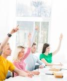 Group of teenage students raising hands Stock Photo