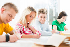 Group of teenage students raising hands Stock Images
