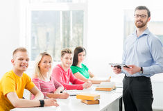 Group of teenage students studying at the lesson in the classroom Stock Photo