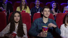 Group of teenager friends at the cinema watching a movie and eating popcorn. Close-up of funny teenagers resting in the cinema, they watch Comedy and eat