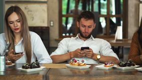 Multi-ethnic group of friends sitting in a restaurant and looking at each of the boredom in your phone