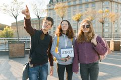 Group teenagers boy and two girls, with a notepad with handwritten word start. Teenagers looking forward, city background, golden royalty free stock images
