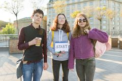 Group teenagers boy and two girls, with a notepad with handwritten word start stock images