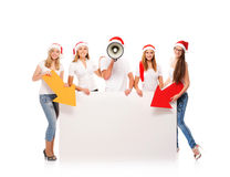 A group of teenagers in Christmas hats pointing on a banner Stock Photos