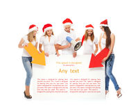 A group of teenagers in Christmas hats pointing on a banner Royalty Free Stock Images