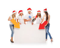 A group of teenagers in Christmas hats pointing on a blank banne. R and using a megaphone. The image is isolated on a white background Royalty Free Stock Photos