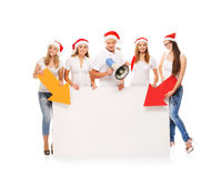 A group of teenagers in Christmas hats pointing on a blank banne. R and using a megaphone. The image is isolated on a white background Royalty Free Stock Images