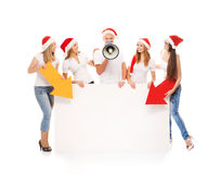 A group of teenagers in Christmas hats pointing on a blank banne Royalty Free Stock Photos