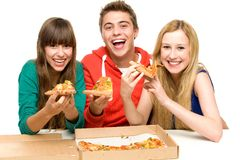 Group Of Teenagers Eating Pizza. Three young people over white background Royalty Free Stock Images