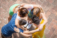 Group of teenagers embraced in circle, aerial view. They are two girls and two boys, looking each other Royalty Free Stock Image