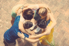 Group of teenagers embraced in circle, aerial view. They are two girls and two boys, looking each other Stock Photo