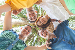 Group of teenagers embraced in circle, bottom view. They are two girls and two boys, smiling and looking down to the camera Stock Images