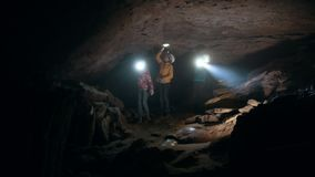 Group of teenagers with flashlights comes into a dark cave