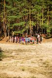 Group of Teenagers in Forest wide vertical. Kyiliv, Kyiv region, Ukraine - 08 09 2017: A group of young people teenagers in a pine forest play rest are competing stock photography