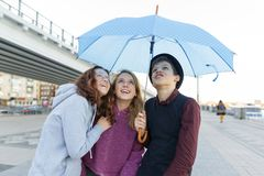 Group of teenagers friends having fun in the city, laughing kids with umbrella. Urban teen lifestyle.  stock image