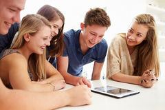 Group Of Teenagers Gathered Around Digital Tablet Together Stock Photography