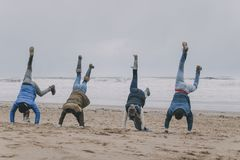 Friends Doing Handstands On A Winter Beach. A group of teenagers have fun on a winter beach doing handstands royalty free stock image