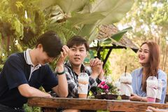 Group of 6 teenagers having fun together without liquor in cafe. In afternoon drink milk tea, pink milk and chocolate in plastic glass Royalty Free Stock Photos